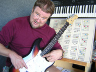 Photograph of Scotty pointing out on his guitar how music theory is applied to the guitar fretboard.